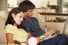 Teenage Boy And Girl Sitting On Sofa At Home Doing Homework Using Laptop Computer Whilst Holding Mobile Phone Stock Photography