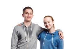 Teenage boy and girl in sweatshirts. Studio shot, isolated. Royalty Free Stock Image
