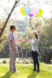 Teenage boy girlfriend. Cute teenage boy giving his girlfriend helium balloons at the park Royalty Free Stock Image