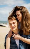Couple on sea side. Teenage boy giving piggyback ride to her girlfriend by the sea Stock Photos