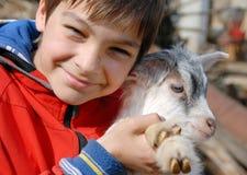 Teenage boy with goatling Stock Photo