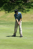 Teenage Boy Golfing. Or putting on the green. He is hitting the ball with a club, he is wearing khaki pants, blue shirt and black hat and shoes Stock Image