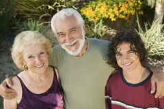 Teenage boy (13-15) with grandparents outdoors elevated view portrait. Stock Image