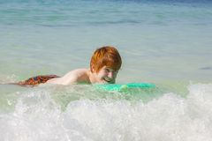 Teenage boy has fun surfing in the waves stock image