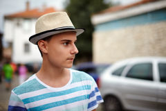Teenage boy with hat outdoor. Closeup of a teenager with hat in an old town, with selective focus Royalty Free Stock Images