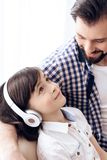 Teenage boy in headphones listens to music, sitting with happy father on couch. stock image