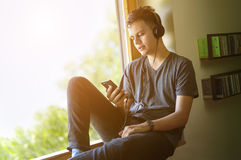 Teenager listening to music on smartphone Stock Image