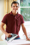 Teenage Boy Helping With Ironing At Home Royalty Free Stock Image