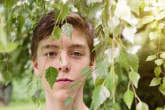 Teenage boy hidden by some leaves Stock Photo
