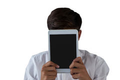 Teenage boy hiding his face behind digital tablet Royalty Free Stock Photography