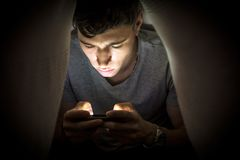 Teenage boy hiding while using a mobile phone Royalty Free Stock Images