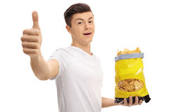 Teenage boy holding bag of chips and making thumb up Royalty Free Stock Images