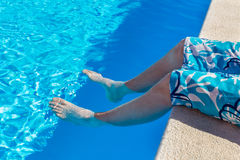 Teenage boy holding bare legs in blue swimming pool. On vacation in summer season Stock Photo