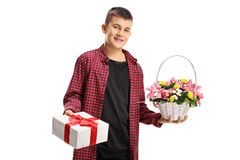 Teenage boy holding a gift box and a basket with flowers royalty free stock images