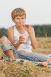 Teenage boy holding glass of milk and straw Stock Image