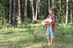 Teenage boy holding hat full of red wildberries Stock Image