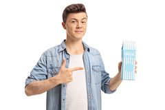 Teenage boy holding a milk carton and pointing. Isolated on white background Royalty Free Stock Images