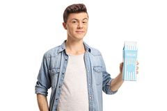 Teenage boy holding a milk carton. Isolated on white background Stock Images