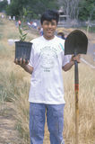 A teenage boy holding a plant and a shovel during Earth Day participation Stock Image