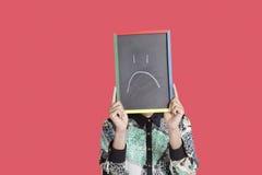 Teenage boy holding sad smiley face sign over pink background Stock Images