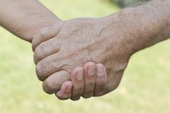 Holding senior man's hand. Teenage boy holding senior man's hand Royalty Free Stock Photo