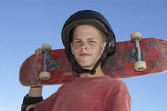 Teenage Boy Holding Skateboard Against Blue Sky. Low angle view of confident teenage boy holding skateboard against blue sky Stock Photos