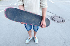 Teenage boy holding skateboard while standing in middle of street Royalty Free Stock Image