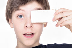 Teenage boy holding a white piece of cardboard Royalty Free Stock Image
