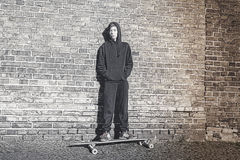 Teenage boy with hoodie standing on a long board Stock Photography