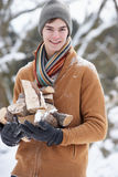 Teenage Boy In Snowy Landscape Carrying Logs Royalty Free Stock Photography