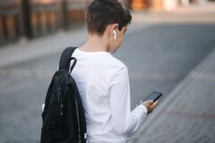 Free Teenage Boy In White Sweatshirt And With Black Backpuck Use Phone And Wireless Headphones And Print Message In Social Stock Image - 188834021