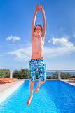 Teenage boy jumping high above blue swimming pool Stock Images