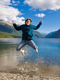 Teenage boy jumping out of water Stock Photography