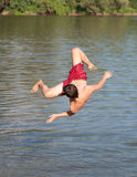 Teenage boy jumping in the river Stock Photo
