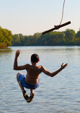 Teenage boy jumping in the river from the rope Royalty Free Stock Photography