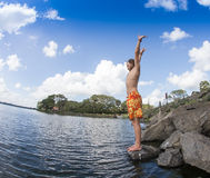 Teenage boy jumping in the river Stock Photography