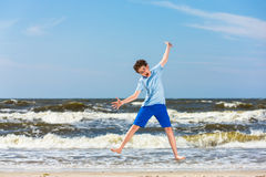 Teenage boy jumping,  running on beach. Young man running, jumping on beach Royalty Free Stock Photos