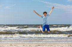 Teenage boy jumping,  running on beach Royalty Free Stock Photography
