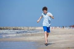 Teenage boy jumping,  running on beach Stock Photography