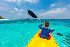 Teenage boy kayaking. Back view of happy teenage boy on a kayak at tropical lagoon Stock Images