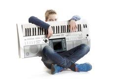 Teenage boy with keyboard in studio Royalty Free Stock Photo