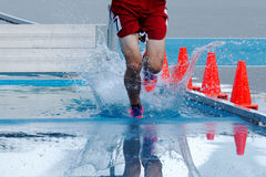 Teenage boy lands in water during a steeplechase race. Landing and splashing in water while racing in the steeplechase Royalty Free Stock Photography
