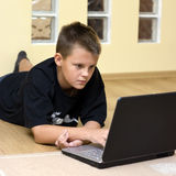Teenage boy and laptop on floor. A white caucasian teenage boy lying down on the floor, using his laptop computer at home royalty free stock photos