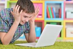 Teenage boy with a laptop Stock Photos