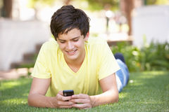 Teenage Boy Laying In Park Using Mobile Phone Stock Photo