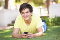 Teenage Boy Laying In Park Using Mobile Phone. At Camera Royalty Free Stock Photos