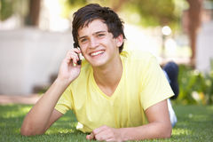 Teenage Boy Laying In Park Using Mobile Phone. Smiling Royalty Free Stock Images