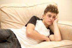 Teenage boy on a sofa. Teenage boy laying on a sofa watching tv Royalty Free Stock Photography