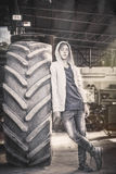 Teenage boy leaning against a huge tire Stock Photography