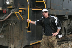 Teenage boy leaning against locomotive Stock Images